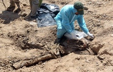 In this file photo taken on April 12th, 2015, a member of the Iraqi security forces wearing protective clothes inspects a mass grave containing the remains of dozens of people believed to have been slain by ISIS at the Speicher camp in Tikrit. ISIS left behind more than 200 mass graves in Iraq containing up to 12,000 victims that could hold vital evidence of war crimes, the UN said November 6th, 2018. [Ahmed al-Rubaye/AFP]