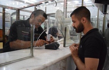 An Iraqi bank teller provides service to a customer on March 14th. [Photo courtesy of Rafidain Bank]