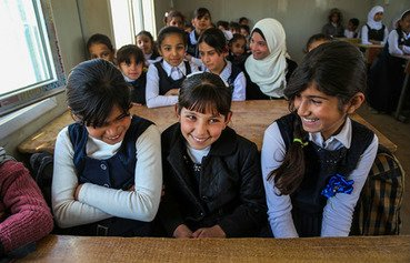 Female students share a desk at a school that was reopened in Fallujah with support from UNICEF. [Photo courtesy of UNICEF]