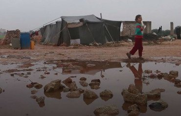 A Syrian girl stands amid the floodwater that has collected in front of her tent in a displacement camp near Saraqeb. [Photo courtesy of Haisam al-Idlibi]