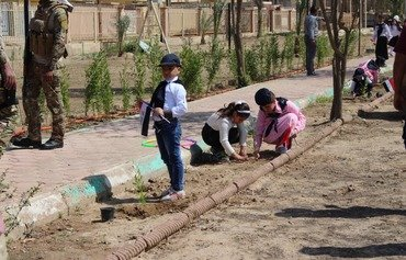 Iraqi youth plant olive trees in Anbar cities